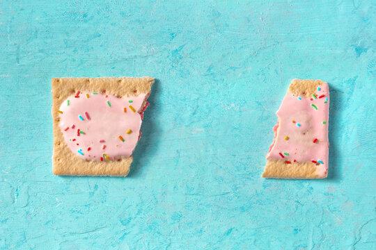 Pop tart, broken, overhead flat lay shot on a blue background