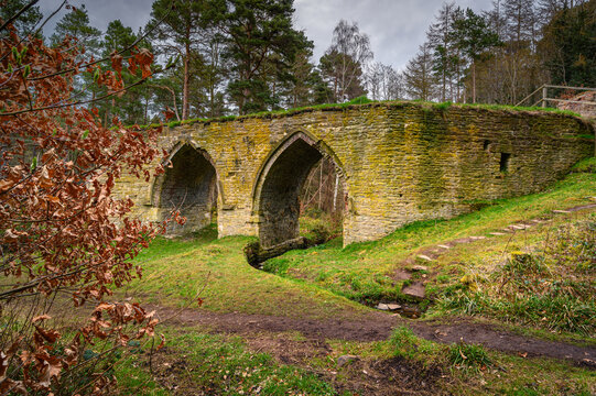 Dukesfield Mill Gothic Arches, the remains of a lead smelting mill which was built in the 18th century, situated in woodland on the banks of Devils Water near Hexham in Northumberland