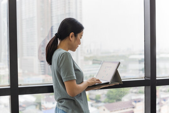 Woman standing next to window holding laptop computer.