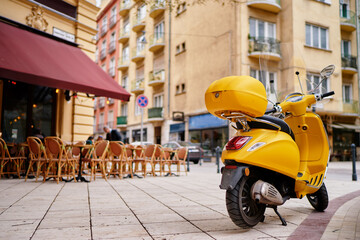 Motorbike outdoor. Yellow retro style scooter on the town street.