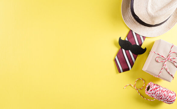 Happy Father's Day background concept with tie and  mustache, hat, gift box on pastel yellow background.