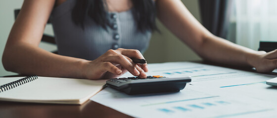Obraz Business woman working in finance and accounting Analyze financial budget with calculator at home - fototapety do salonu