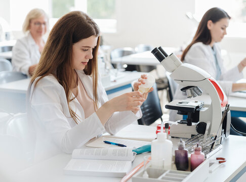 Researchers in white coats working in lab