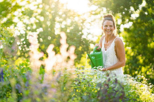 Portrait of young woman watering flowers in springtime garden