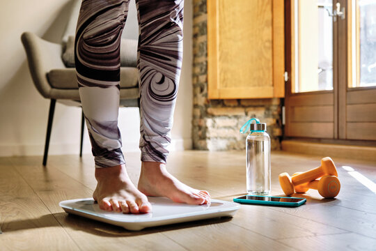 Woman analyzing weight while standing on weight scale at home
