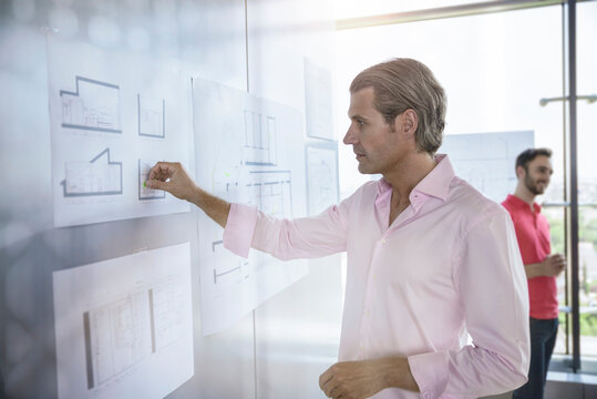 Confident male architect working with graph on white board in office