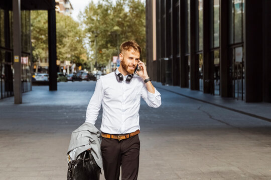 Businessman talking on mobile phone while walking on footpath