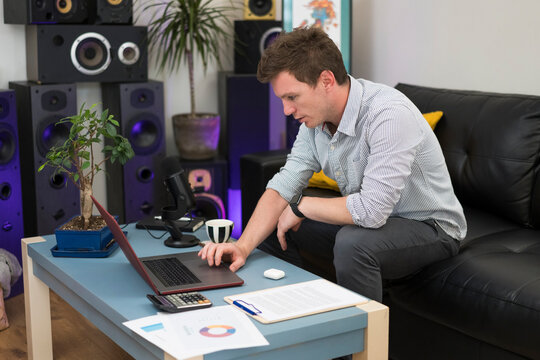 Businessman working on laptop while sitting on sofa at home