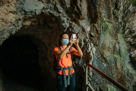 Hiker wearing face mask using mobile phone while standing by underpass at Cares Trail in Picos De Europe National Park, Asturias, Spain
