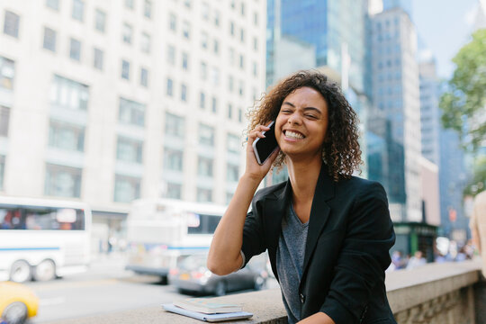 Happy young businesswoman talking on smart phone in city