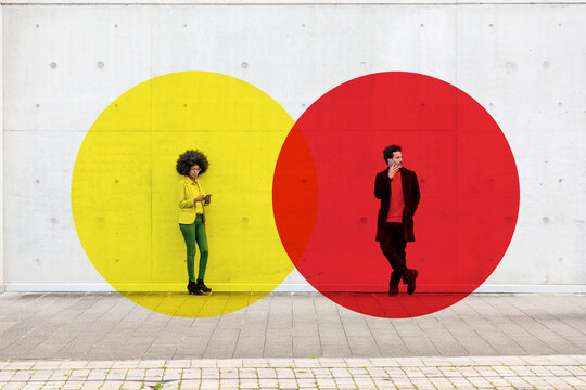 Two overlapping circles visualizing social distancing covering man and woman standing outdoors with smart phones in hands