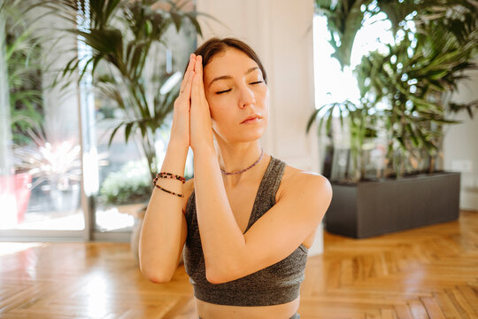 Beautiful woman meditating with clasped hands at home