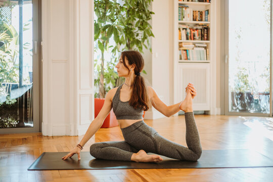 Flexible woman stretching legs while practicing yoga at home