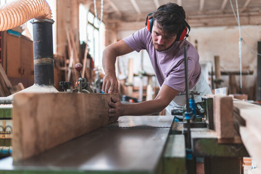 Young male craftsperson holding wooden plank on workbench while working in workshop