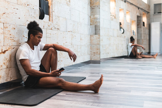 Young man sitting with mobile phone on exercise mat against wall at health club