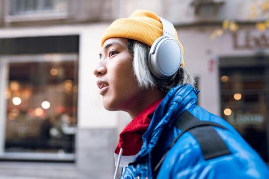 Asian man listening music through headphones outdoors