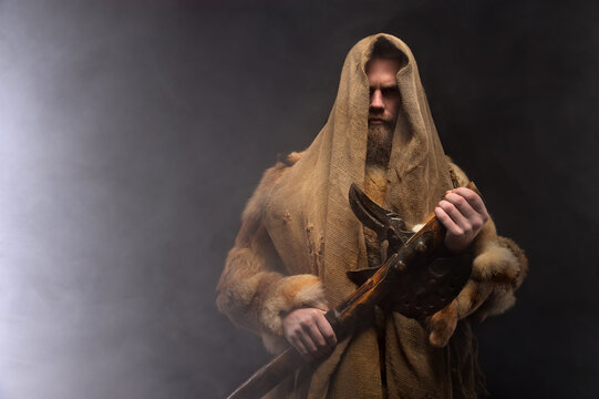 Copy space portrait mysterious man in robes and furs stands and holds an ancient ax in his hands, a dark room with smoke