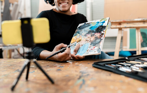 Young female artist showing paint palette while vlogging through smart phone at studio