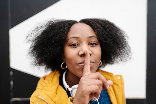 Young woman with finger on lips against wall