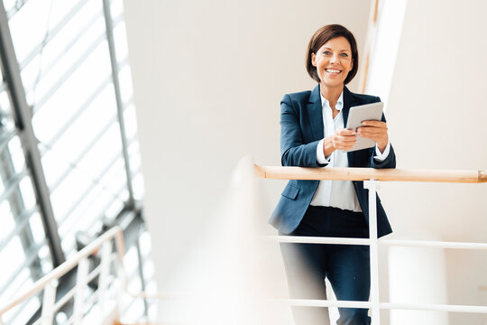 Happy businesswoman with digital tablet leaning on railing at corridor