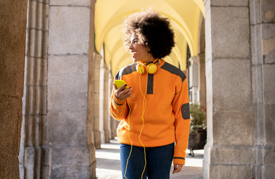 Cheerful woman with mobile phone and headphones looking away while walking at corridor