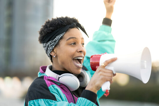 Young woman doing announcement through megaphone