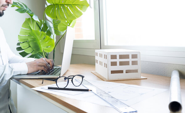Young male architect using laptop at desk in office
