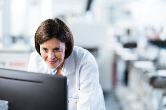 Smiling female engineer using computer at factory