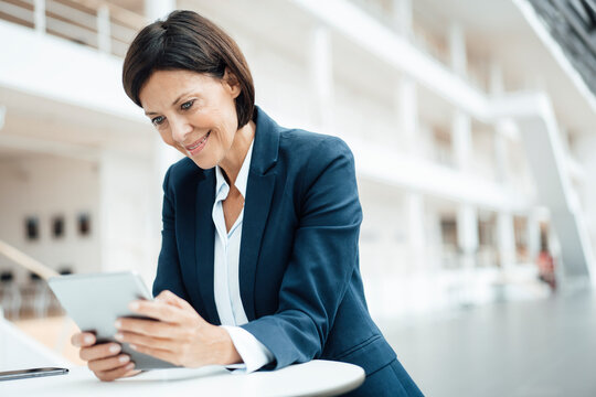 Smiling businesswoman using digital tablet while working in office