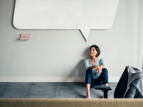 Thoughtful businesswoman looking up while sitting on floor at office