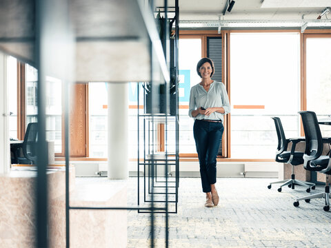 Happy female entrepreneur with smart phone standing at office