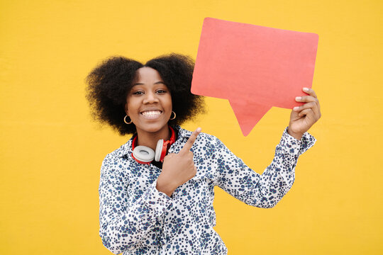 Young woman pointing at speech bubble against yellow wall