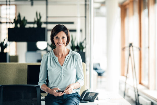 Happy businesswoman with smart phone in office