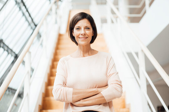 Smiling confident businesswoman with arms crossed against steps in corridor