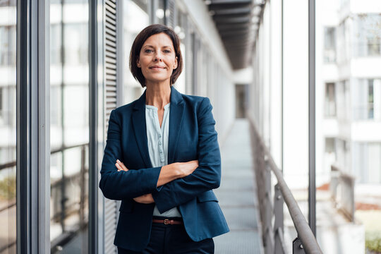 Smiling confident businesswoman with arms crossed standing on balcony