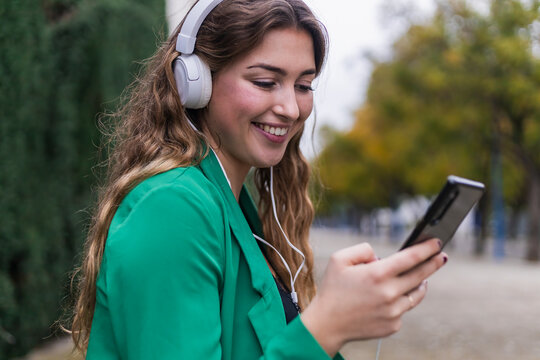 Young woman using smart phone while listening music through headphones in park