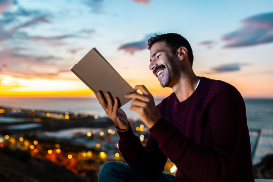 Happy man in maroon sweater reading book against sky during sunrise