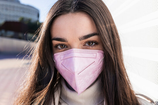 Teenage girl with protective face mask on sunny day