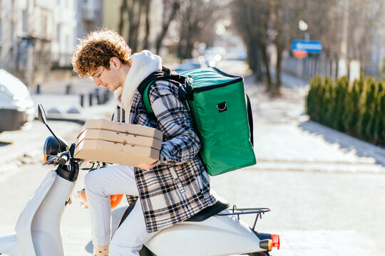 Curly red haired delivery man preparing to giving pizza boxes to customer. Handsome food delivery courier pulls out an order while standing near his scooter and wearing green thermal backpack.