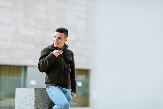 Smiling young man using smart phone while leaning on bench