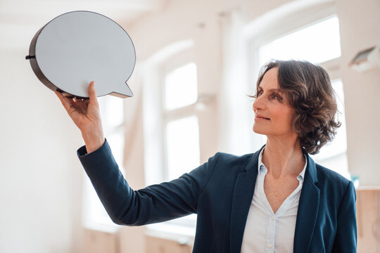 Smiling businesswoman holding speech bubble at home office