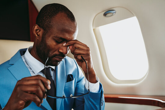 Young businessman emotionally stressed traveling in private jet