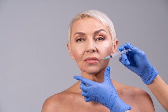 Doctor injecting senior woman lip while standing against gray background
