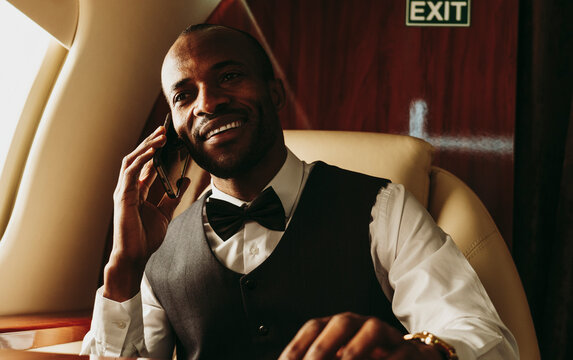Young businessman talking on mobile phone while traveling in private jet