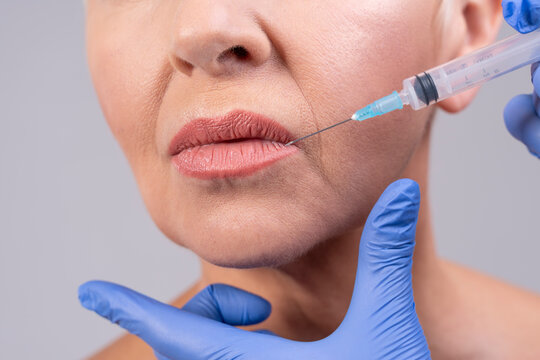 Doctor hands injecting woman lip against gray background