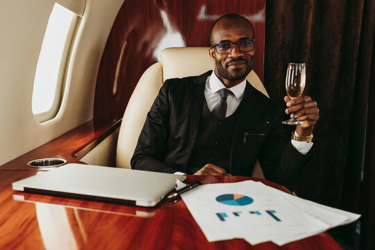 Smiling businessman holding champagne by laptop and document in airplane