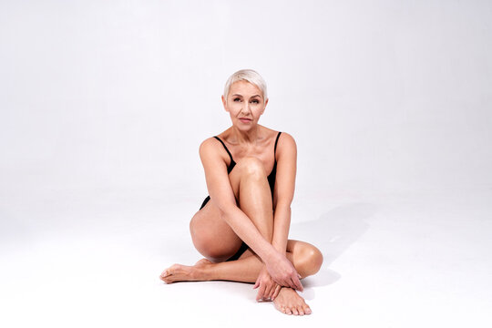 Senior woman in bodysuit staring while sitting against gray background
