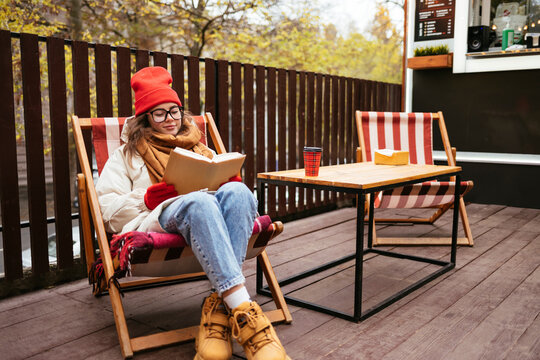 Young woman wearing warm clothing reading book while sitting on chair at sidewalk cafe