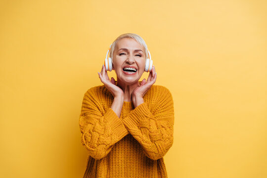 Smiling woman wearing headphones standing against yellow background