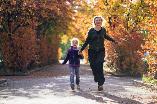 Happy mother and daughter holding hands and running in park during autumn